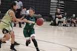 Muskogee girl's basketball player dribbles around a defender.